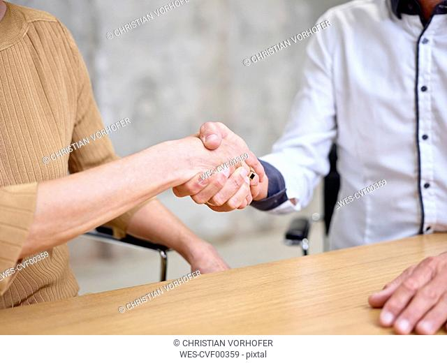 Close-up of businessman and businesswoman shaking hands