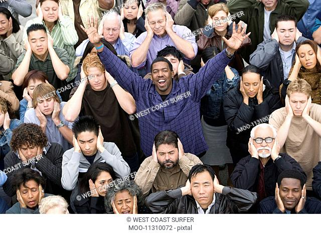 Man celebrating among crowd covering ears