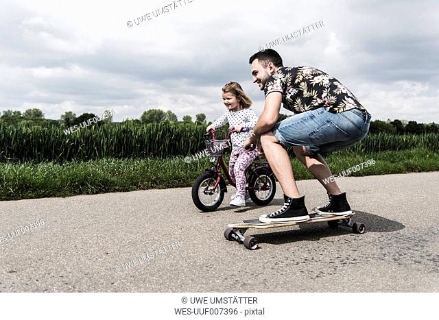 Father on skateboard accompanying daughter on bicycle