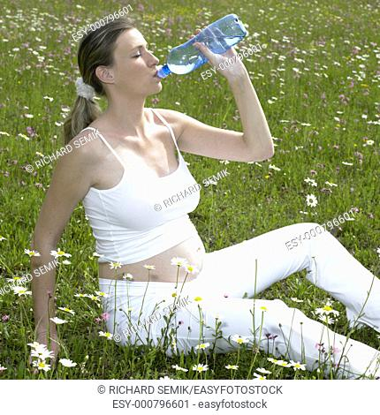 pregnat woman on meadow with bottle of water