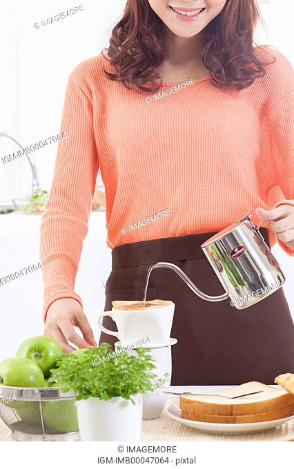 Young woman making coffee with smile