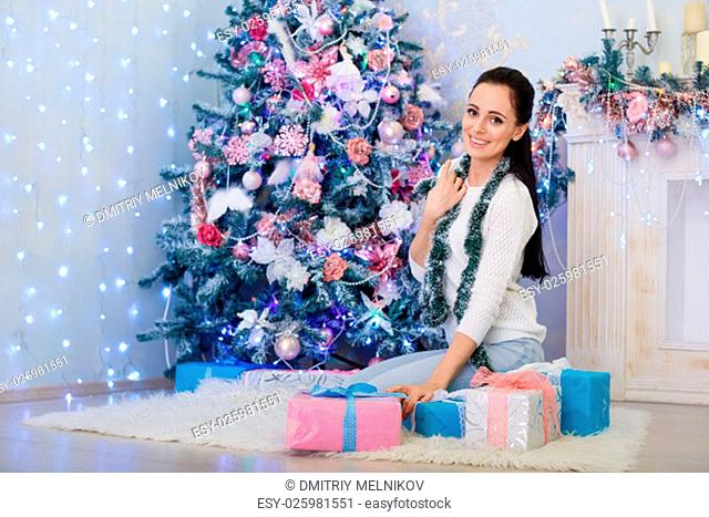 Young happy beautiful woman with gift boxes sits near Christmas tree in the room of the house. Merry Christmas and New Year