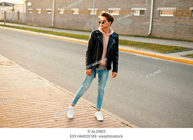 Fashionable young handsome man with sunglasses in a leather jacket, blue jeans and white sneakers near the road