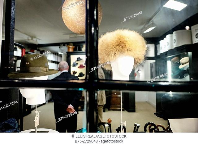 Hat shop, display of hats in shop window, unrecognizable old man standing inside. James Lock and Co., London, England