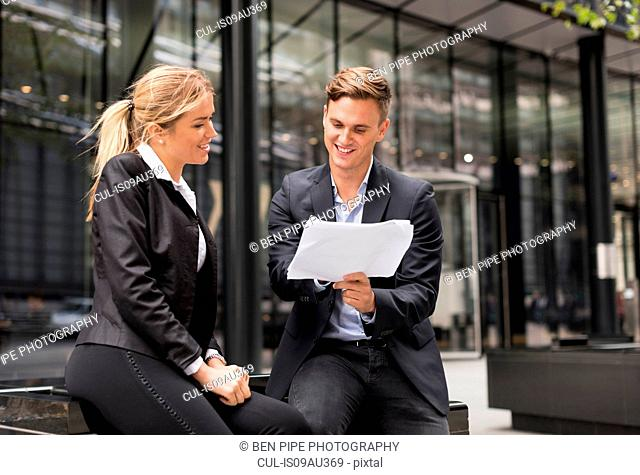 Businessman and businesswoman meeting outside office building, London, UK