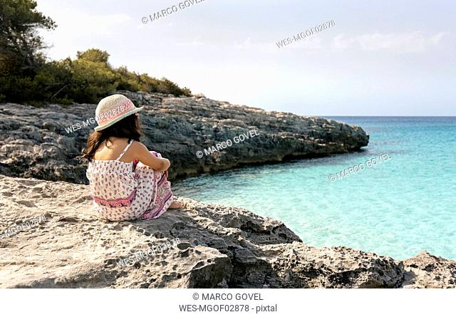 Girl sitting at the beach looking at the sea