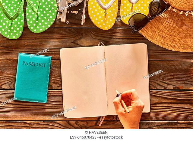 Planning a beach trip. Woman's hands with pencil over blank notebook. Travel items for beach tourism still life over wooden background
