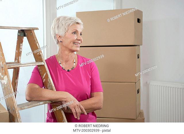 Senior woman standing with step ladder in new apartment, Bavaria, Germany