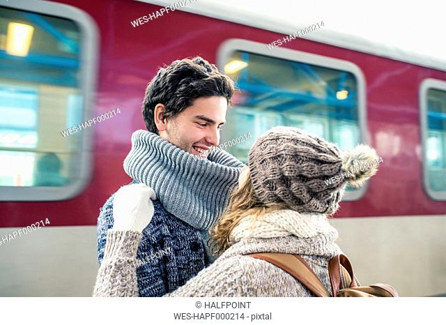 Happy young couple in front of train