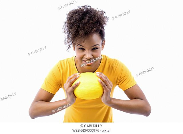 Portrait of young woman with honeydew melon in front of white background