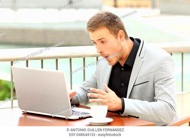 Amazed businessman receiving good news sitting in a coffee shop