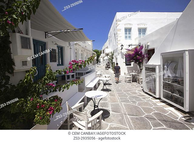 Local man walking through the whitewashed houses with colorful doors and windows in the town center, Naoussa, Paros, Cyclades Islands, Greek Islands, Greece