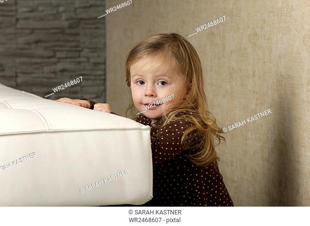 Little girl behind a sofa