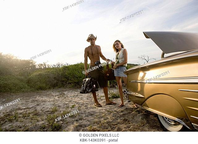 View of a young couple standing by antique convertible car