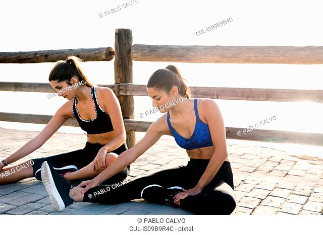 Two young women training on waterfront, touching toes