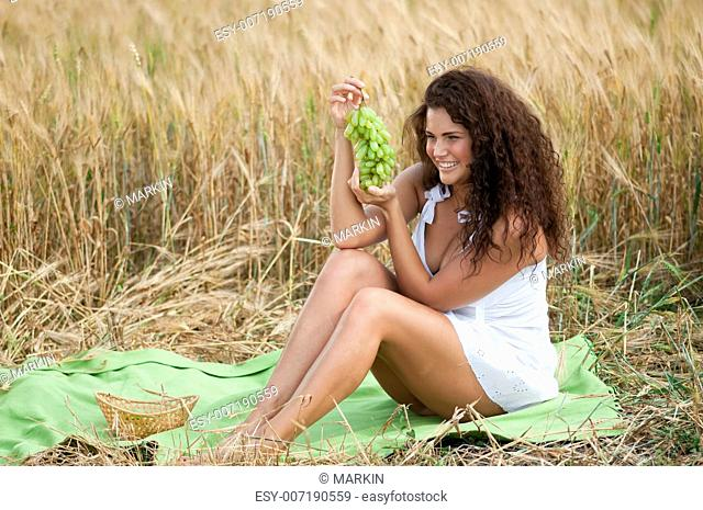 Beautiful woman with perfect hair and skin posing in wheat field and eating green grapes. Picnic