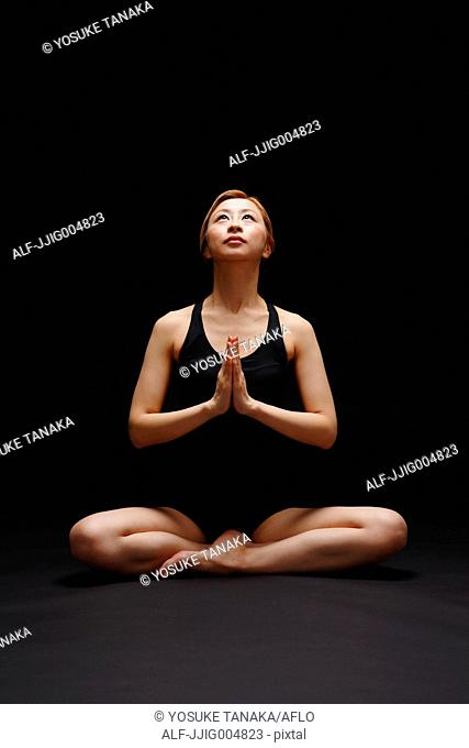 Attractive young Japanese woman wearing black pants and tank top practicing yoga on black background