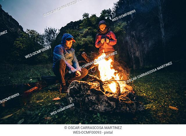 Couple with with bikes at camp fire