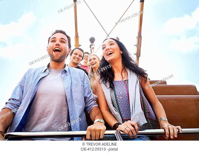 Enthusiastic couple riding amusement park ride