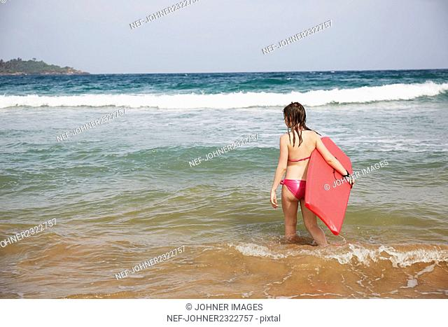 Girl with swimming board in sea