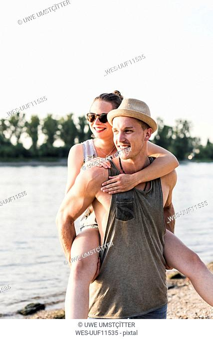 Young man giving girlfriend piggyback ride at the riverbank