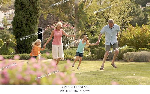 Panning shot of grandparents and two granddaughters walking in park