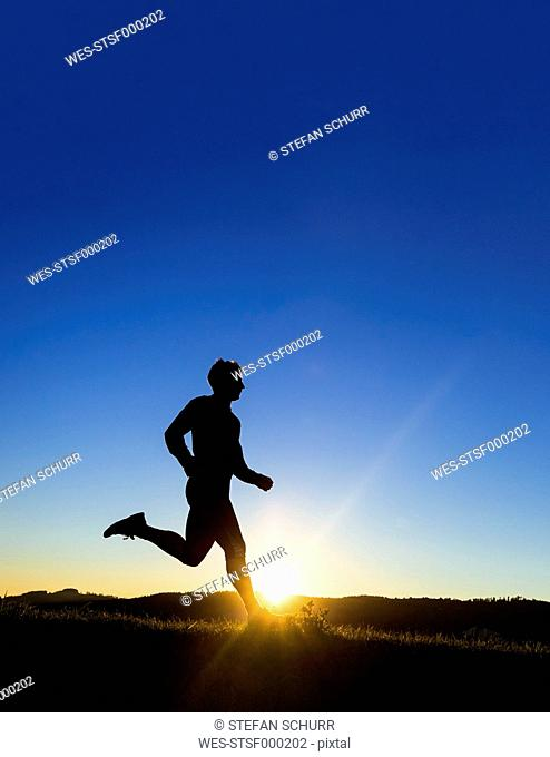 Germany, Winterbach, jogger at sunset