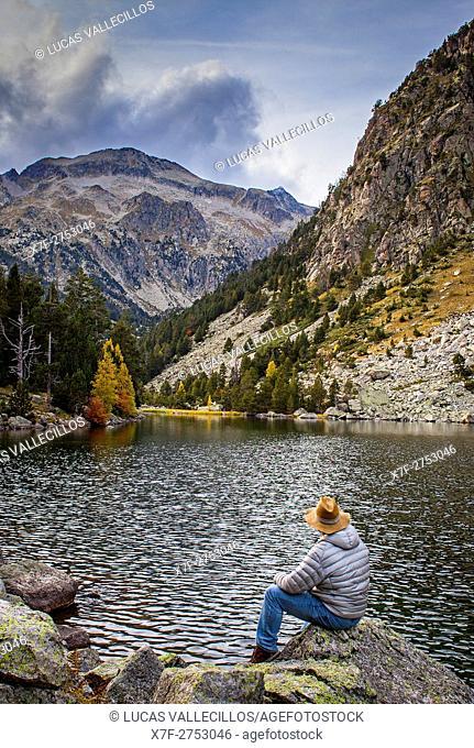 Hiker. `Estany Llong',Llong lake,Aigüestortes i Estany de Sant Maurici National Park,Pyrenees, Lleida province, Catalonia, Spain