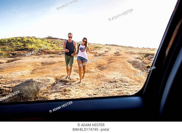 Caucasian couple walking toward car