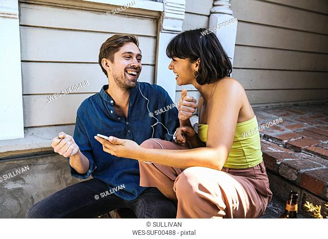 Happy young man and woman with smartphone and earphones