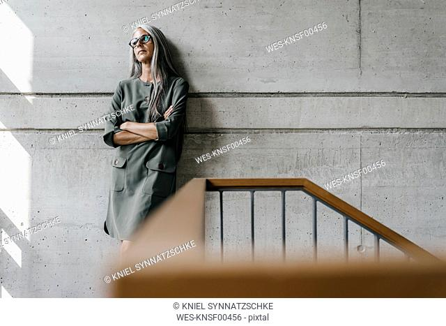 Woman with long grey hair leaning against a wall