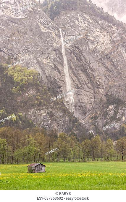 Beauty landscape. Wooden cottage in background big mountain and waterfall - France