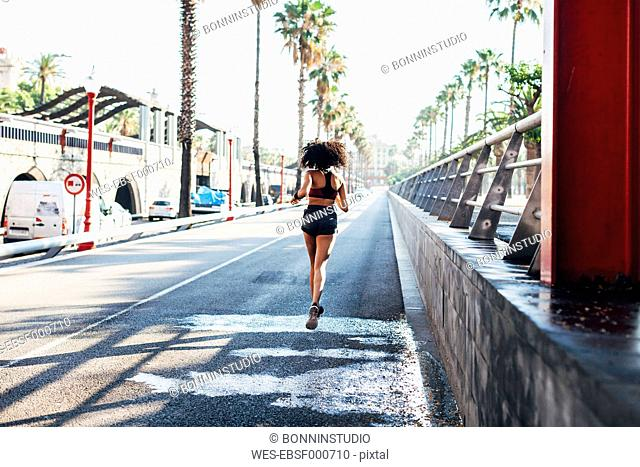 Spain, Barcelona, back view of jogging young woman on a street