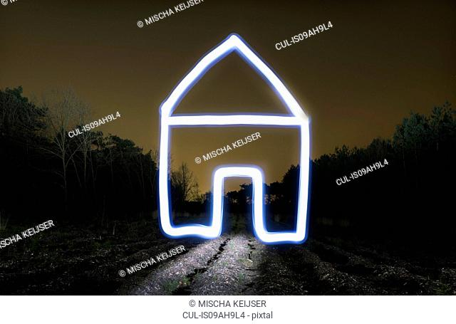 Field landscape at night with light painted drawing of house