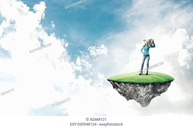 Beautiful woman traveler in hat with suitcase on green island floating in air