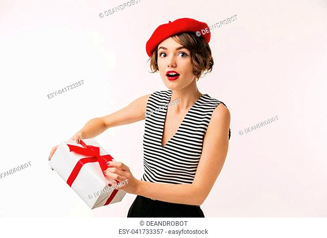 6ca75941a15 Portrait of a surprised woman wearing red beret holding present box  isolated over white background