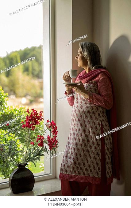 Older woman standing at window with cup of tea