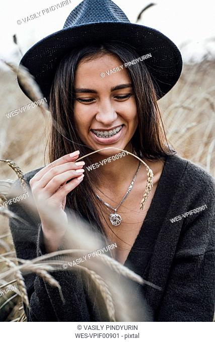 Portrait of laughing young woman dressed in black in a corn field