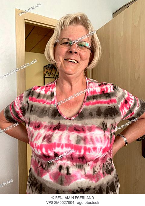 positive senior woman with arms akimbo at home, in Cottbus, Germany