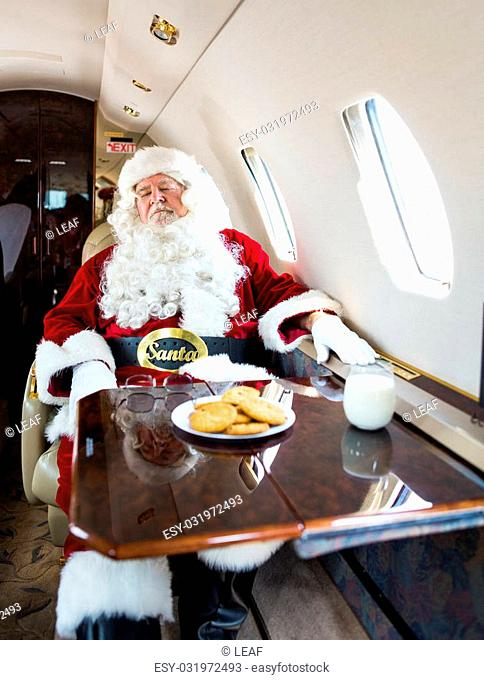 Man in santa costume relaxing on private jet