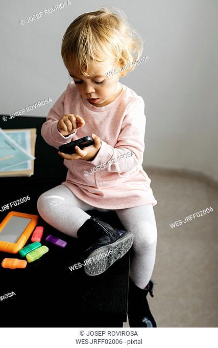 Little girl using mobile phone, sitting on desk