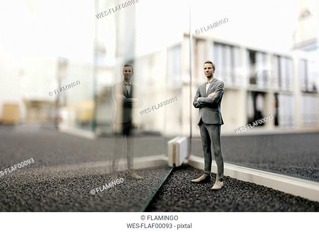 Businessman figurine standing in front of glass wall in office