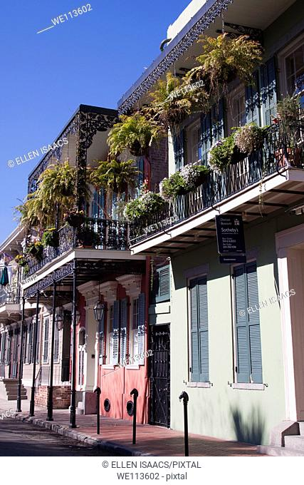 Creole townhouses with ornate wrought iron balcony and hanging planters and window boxes in the French Quarter of New Orleans, Louisiana
