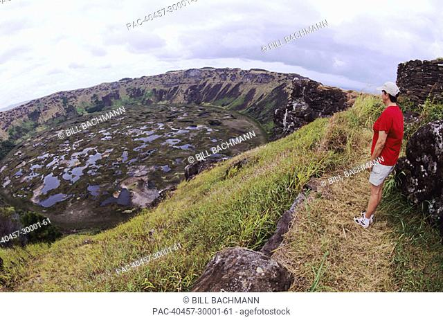 Easter Island, Rano Kau Crater, hiker on trail at edge of cliff