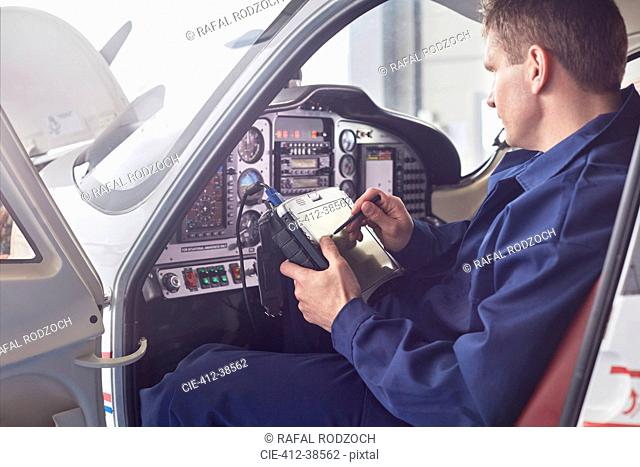 Male engineer checking diagnostics with digital tablet in airplane cockpit