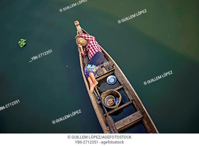 A local fisherwoman sleeping in her boat at the Taungthaman Lake, Amarapura, Myanmar