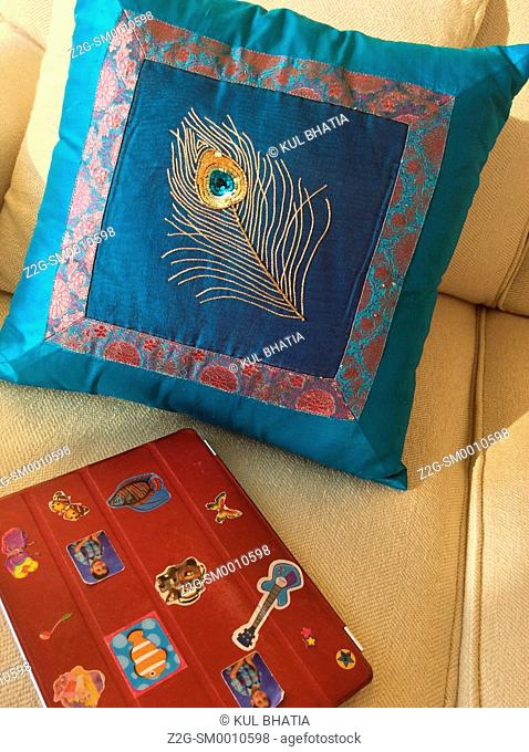 An artistic peacock-feather design on a luxury cushion, a tablet with stickers in the foreground, Ontario, Canada