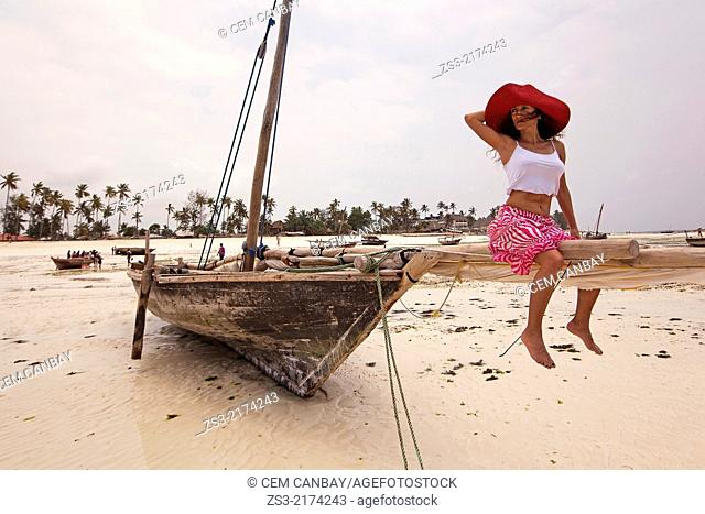 Woman sitting on a dhow at Nungwi beach, Nungwi, Zanzibar Island, Tanzania, Indian Ocean, East Africa