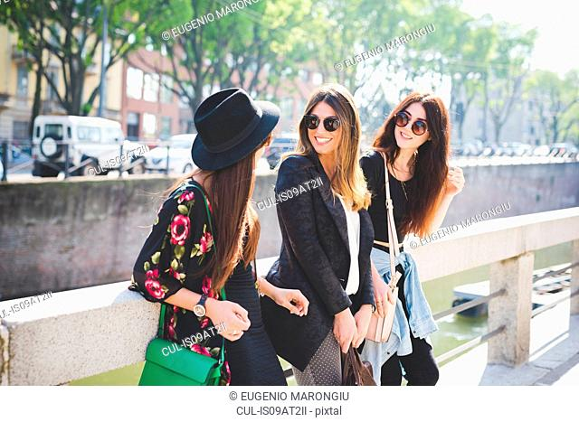 Three stylish young female friends chatting on city riverside
