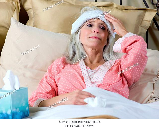 Sick older woman laying in bed